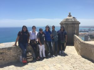group photo of students in spain with ocean behind them